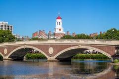 蓝色波士顿桥梁校园查尔斯时钟哈佛约翰在河天空塔结构树大学w星期 几星期跨接与在查尔斯河的钟楼 免版税图库摄影
