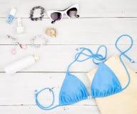 蓝色泳装、黄色短裤、化妆用品构成、珠宝和精华在白色木书桌上 库存照片