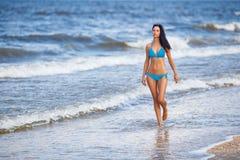 蓝色泳装的美丽的苗条妇女走在海滩的 库存照片