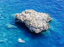 蓝色海、岩石和从从奥古斯都庭院看见的休闲小船 库存图片