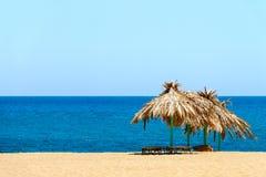 蓝色海、金黄沙子和sunbeds在海滩 免版税库存照片