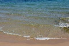 蓝色海和沙子的光波在一个晴天靠岸 免版税库存照片