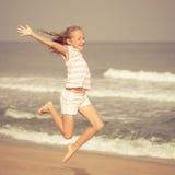 蓝色海岸的飞行的跳跃的海滩女孩 库存照片