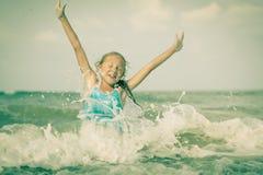 蓝色海岸的飞行的跳跃的海滩女孩 免版税库存图片
