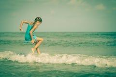 蓝色海岸的飞行的跳跃的海滩女孩 图库摄影