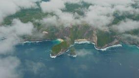 蓝色海洋,波浪,有山的热带海岛鸟瞰图通过云彩 股票录像