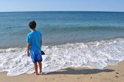 蓝色海滩的男孩 免版税库存照片