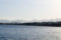 蓝色海的风景水表面的以遥远的山和一个热带村庄为背景 免版税库存图片