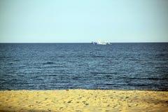 蓝色海,黄沙,白色船 图库摄影