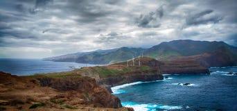 蓝色海洋、山、岩石、风车和多云天空 库存照片