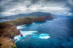 蓝色海洋、山、岩石、风车和多云天空 免版税库存图片