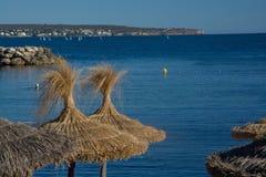 蓝色海洋和秸杆棕色遮阳伞 免版税图库摄影