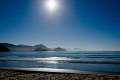 蓝色海滩在蓝天下 免版税图库摄影