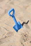 蓝色海滩铁锹在沙子黏附了由孩子 免版税图库摄影