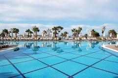 蓝色游泳池、sunbeds和棕榈树看法在beac附近 免版税图库摄影