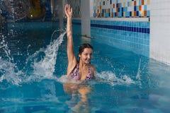 蓝色游泳池的女孩与飞溅和下落 免版税库存照片