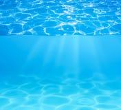 蓝色游泳池水表面和水下 库存照片