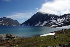 蓝色湖在用雪盖的山的脚在夏天在挪威 库存照片