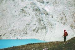 蓝色湖山的旅客与背包远足 免版税库存图片
