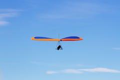 蓝色滑翔机吊桔子 免版税库存图片