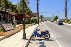 蓝色滑行车自行车停留停放在罗得岛海岛上的传统希腊小酒馆附近 免版税图库摄影
