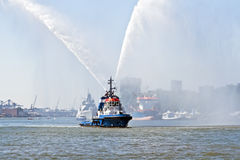 蓝色火小船喷洒的水在鹿特丹港口荷兰 库存照片