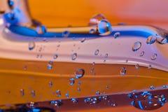 蓝色点燃了桔子铬版表面上的watter小滴 免版税图库摄影