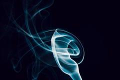 蓝色烟漩涡在黑背景的 免版税库存图片