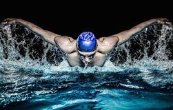 蓝色焰晕的人在游泳池 库存图片