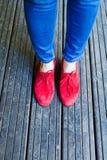 蓝色牛仔布和红色鞋子 库存照片