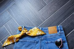 蓝色牛仔布衣裳、太阳镜、动物印刷品传送带和时髦芥末黄色丝带头发的在木背景 库存图片