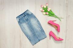 蓝色牛仔布裙子、桃红色郁金香鞋子和花束  时兴 库存照片