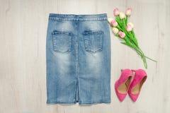 蓝色牛仔布裙子、桃红色郁金香鞋子和花束  时兴 图库摄影
