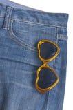 蓝色牛仔布重点矿穴形状的太阳镜 免版税库存照片