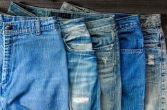 蓝色牛仔裤和斜纹布缺乏在木地板上的纹理 免版税库存图片