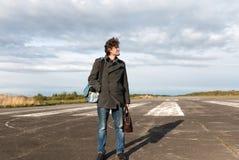 蓝色牛仔裤和灰色外套的年轻人站立在跑道去休假在有棕色皮包的空中飞机上的 免版税库存图片