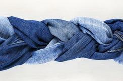 蓝色牛仔裤时髦的被编织的辫子在白色木背景的 库存图片