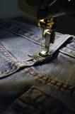 蓝色牛仔裤用机器制造缝合 免版税图库摄影