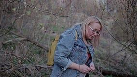 蓝色牛仔裤的一个女孩通过在弯曲她的头的树枝下 美好的电影框架   股票视频