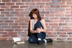 蓝色牛仔裤的年轻美丽的姜头发妇女读书的,当坐地板在红砖墙壁附近时 免版税库存照片