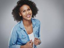 蓝色牛仔布的俏丽的微笑的妇女 库存图片