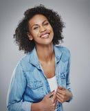 蓝色牛仔布的俏丽的笑的妇女 图库摄影
