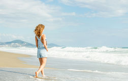 蓝色牛仔布连衫裤的少妇走沿海滩的和风雨如磐的海洋在晴天 库存图片