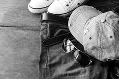 蓝色牛仔裤、盖帽和鞋子在老木背景 图库摄影