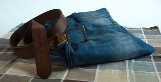 蓝色牛仔裤和棕色传送带 库存照片
