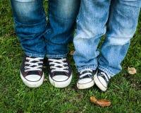 蓝色牛仔裤和黑白鞋子成人和孩子 图库摄影