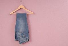 蓝色牛仔裤在挂衣架 库存照片