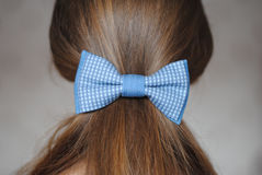 蓝色牛仔裤在长的头发女孩的簪子弓 库存照片
