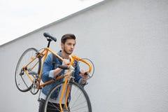 蓝色牛仔裤夹克的人继续他的肩膀桔子自行车 一个年轻人固定 免版税库存照片