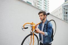 蓝色牛仔裤夹克的人继续他的肩膀桔子自行车 一个年轻人固定 库存照片
